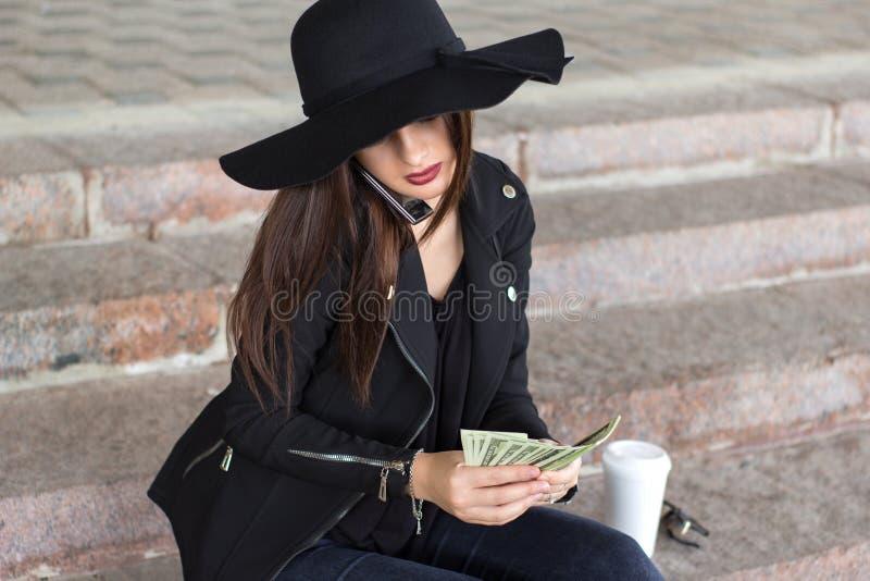 Muchacha en una chaqueta hecha a ganchillo y un sombrero negro foto de archivo libre de regalías