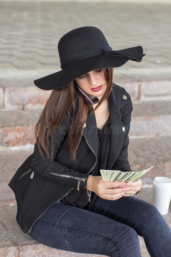 Muchacha en una chaqueta hecha a ganchillo y un sombrero negro imágenes de archivo libres de regalías