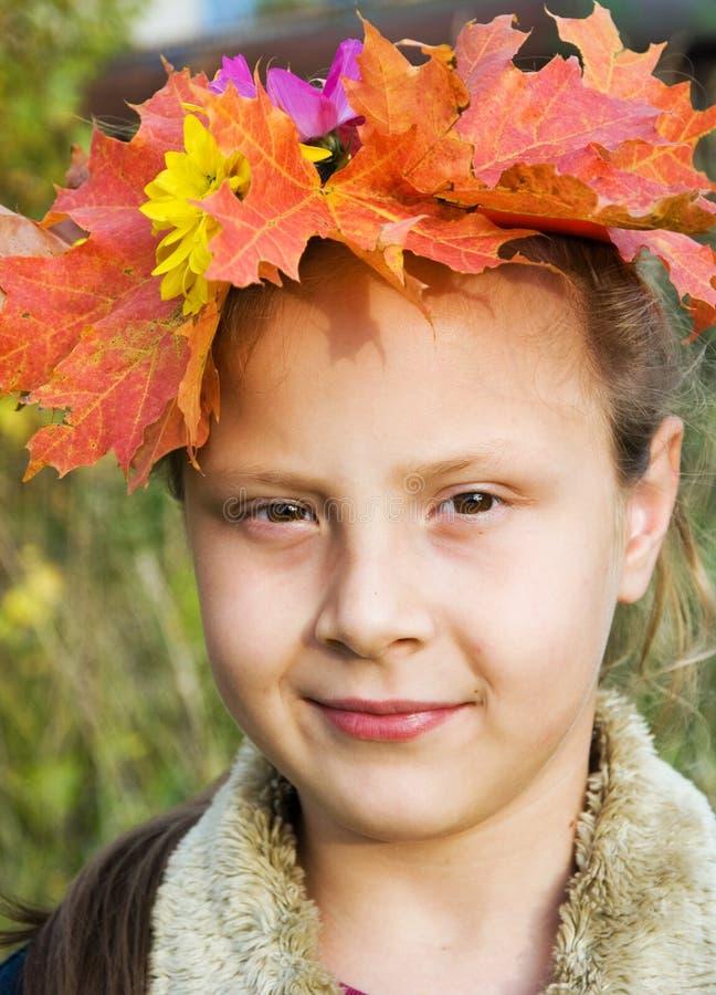 Muchacha en una guirnalda de las hojas de otoño fotografía de archivo libre de regalías