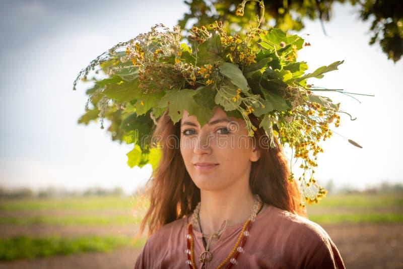 Muchacha en una guirnalda de las hojas y de las flores del roble Símbolo de la unidad con la naturaleza fotos de archivo libres de regalías