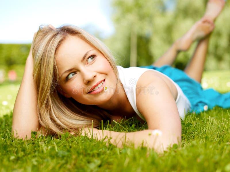 Muchacha en una hierba (imagen media del formato) fotos de archivo