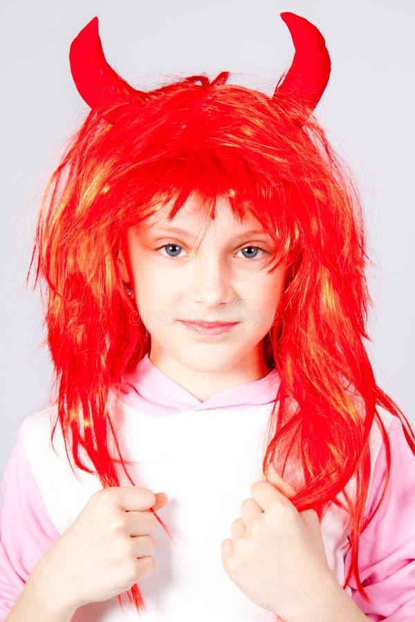 Muchacha en una peluca roja con los pequeños claxones imagenes de archivo
