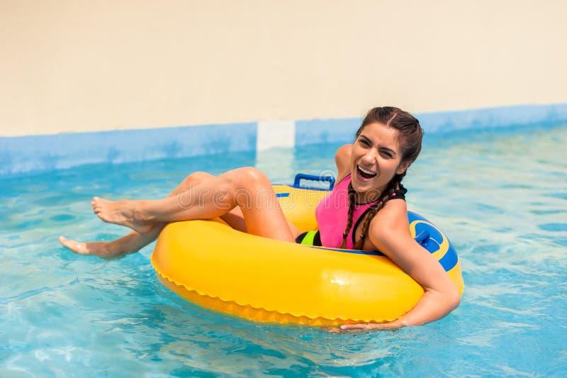Muchacha en una piscina que se sienta en un flotador inflable de goma imagenes de archivo