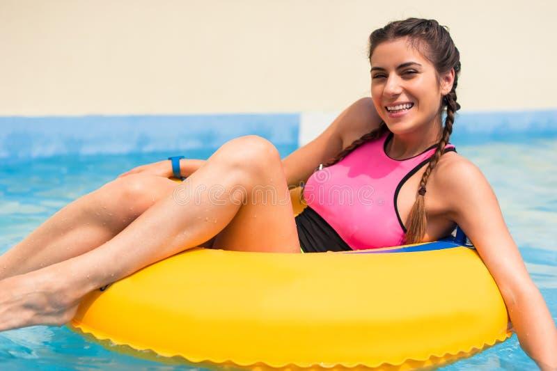 Muchacha en una piscina que se sienta en un flotador inflable de goma imagen de archivo libre de regalías