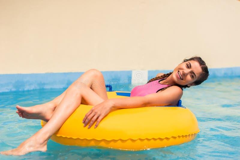Muchacha en una piscina que se sienta en un flotador inflable de goma imágenes de archivo libres de regalías