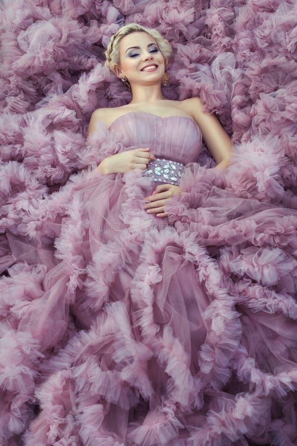 Muchacha en una sonrisa rosada del vestido imagen de archivo libre de regalías