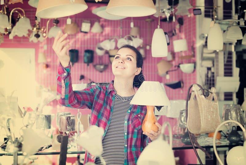 Muchacha en una tienda más ligera que elige la lámpara de cristal moderna para la casa foto de archivo libre de regalías