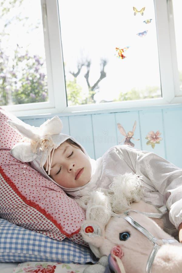 Muchacha en Unicorn Costume Sleeping In Bed fotografía de archivo libre de regalías