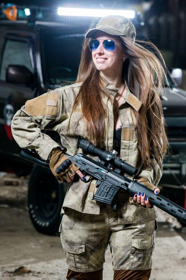 Muchacha en uniforme con las armas en sus manos fotos de archivo libres de regalías