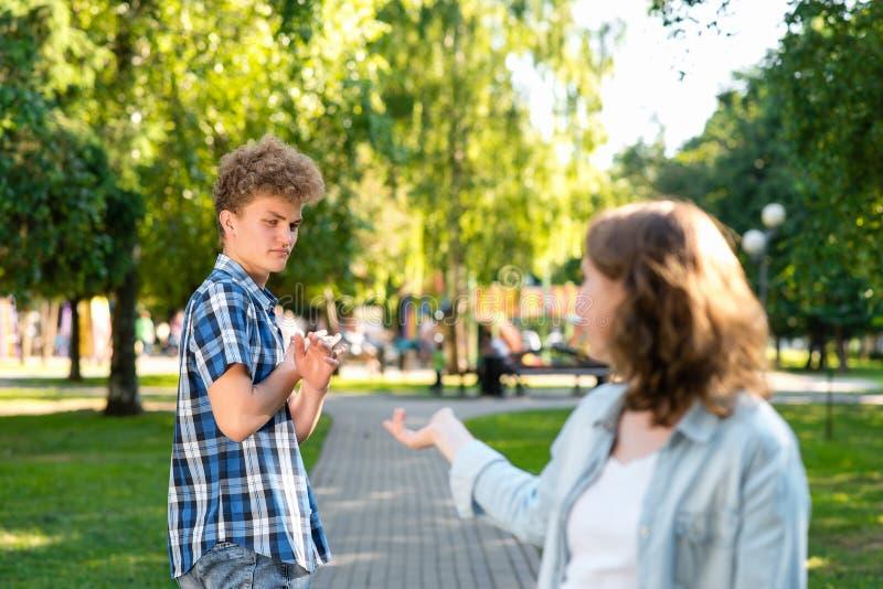 Muchacha en verano en una naturaleza del parque Intenta conseguir conocido con un hombre joven Los gestos del individuo para most fotos de archivo libres de regalías