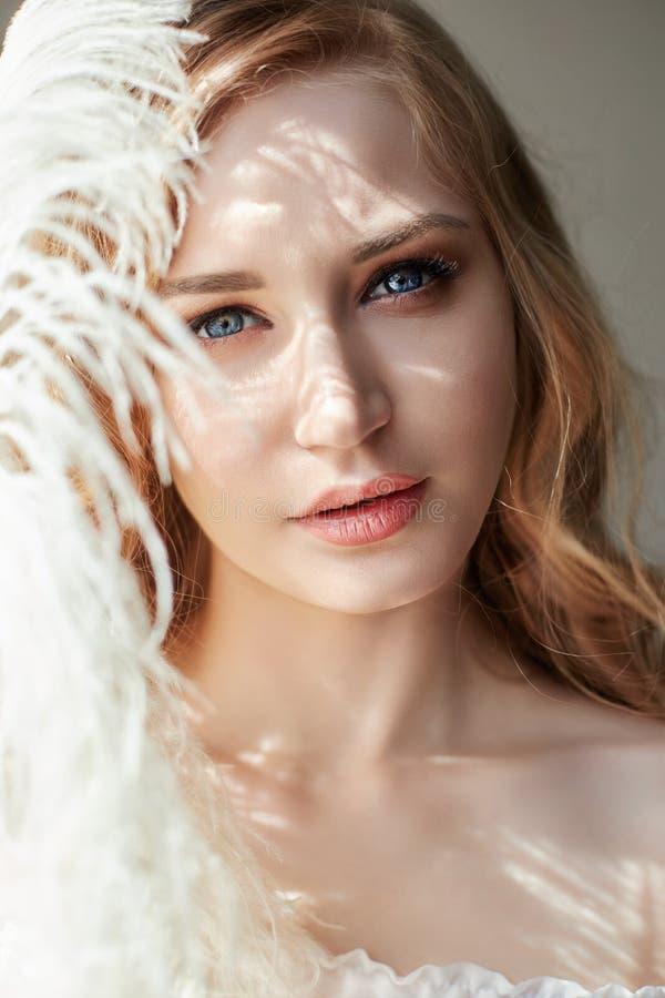 Muchacha en vestido de la luz blanca y pelo rizado con la pluma grande cerca de su cara, mujer del retrato con la pluma, pureza e imagen de archivo