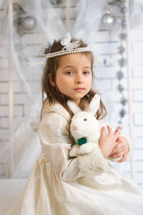 Muchacha en vestido de las vacaciones de invierno con el conejo del juguete fotos de archivo libres de regalías