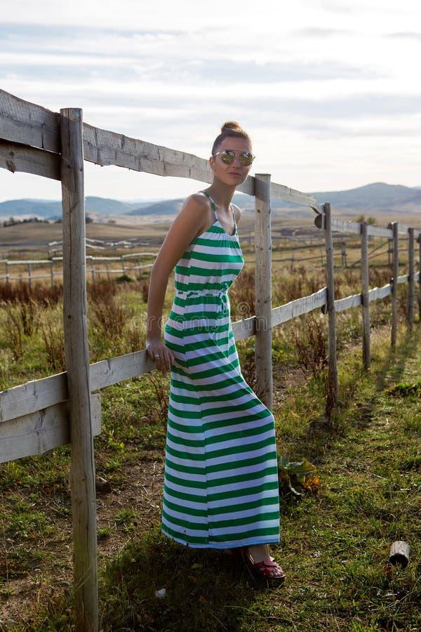 Muchacha en vestido del verde largo en el pueblo en la cerca por la mañana imagenes de archivo