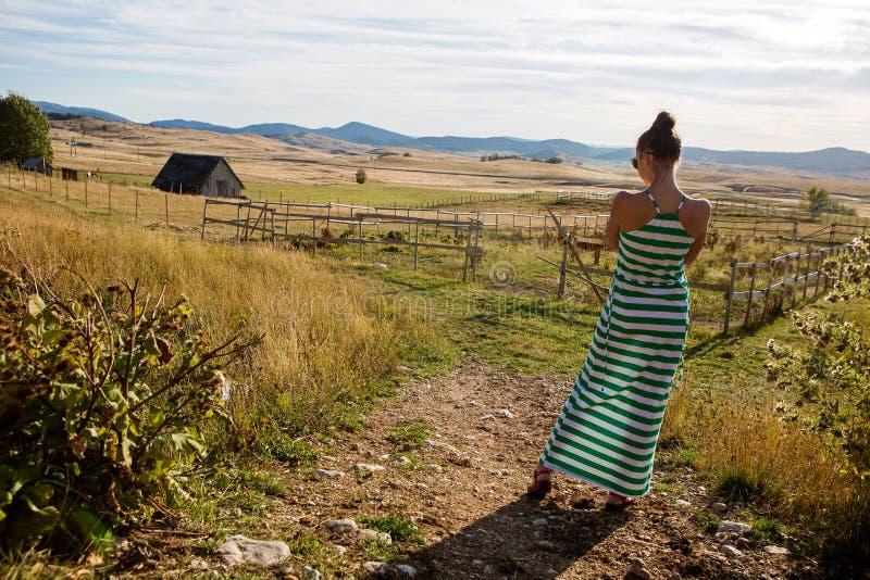 Muchacha en vestido del verde largo en el pueblo en la cerca por la mañana foto de archivo