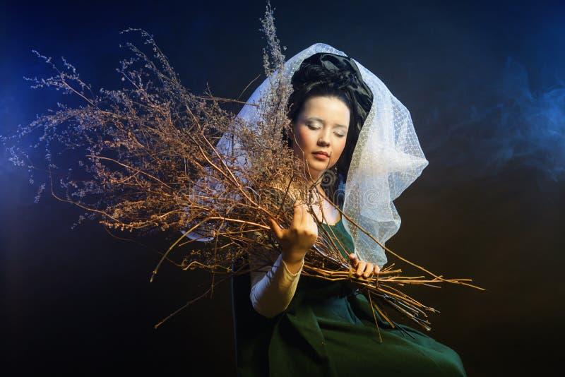 Muchacha en vestido medieval con el manojo de palillos foto de archivo libre de regalías