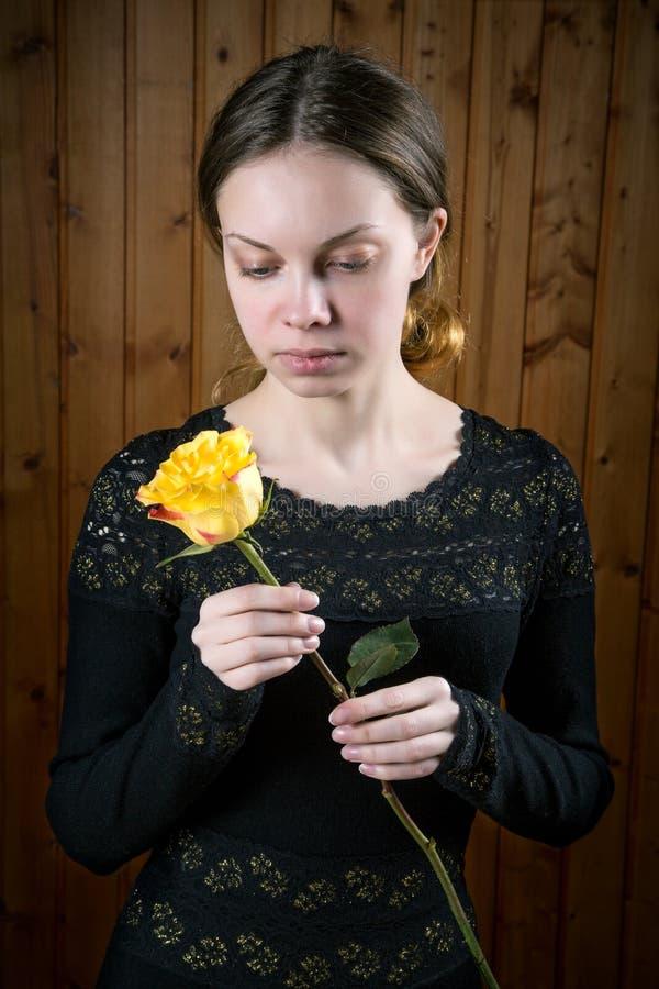 Muchacha en vestido negro con la rosa del amarillo imagenes de archivo
