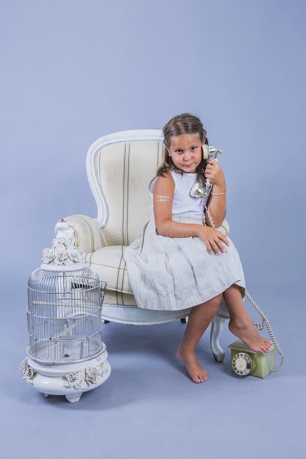 Muchacha en vestido que habla con el teléfono viejo con la cara sorprendida fotos de archivo