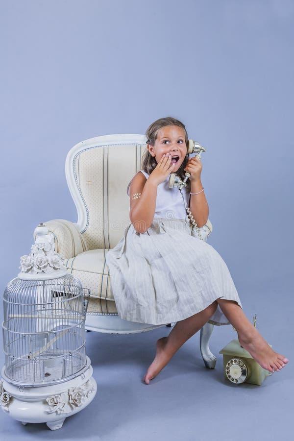 Muchacha en vestido que habla con el teléfono viejo con la cara sorprendida foto de archivo