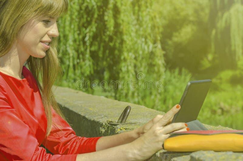 Muchacha en vestido rojo con la tableta imagen de archivo libre de regalías