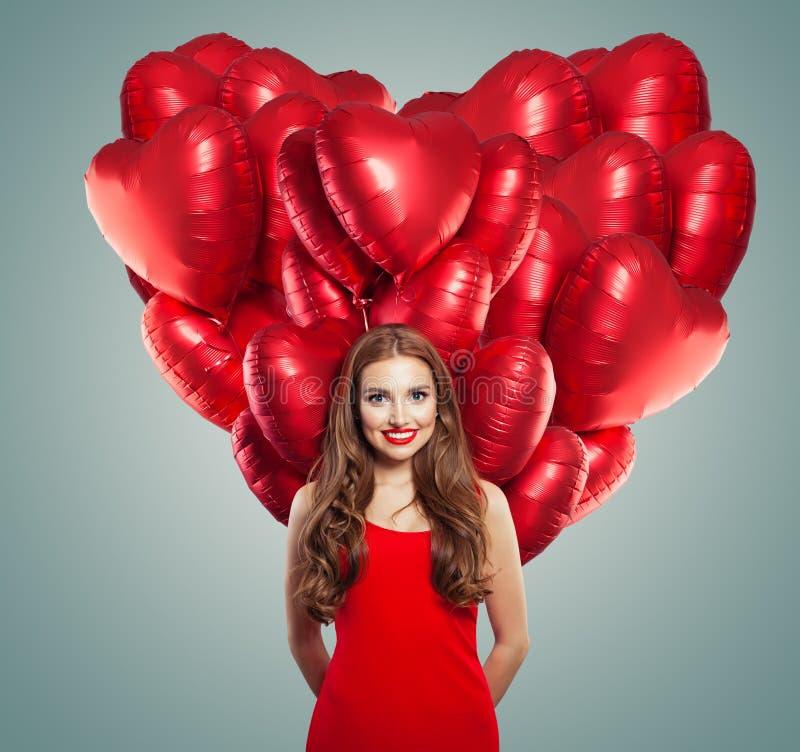 Muchacha en vestido rojo con los globos del corazón Mujer hermosa con maquillaje rojo de los labios, pelo rizado perfecto y sonri fotografía de archivo libre de regalías