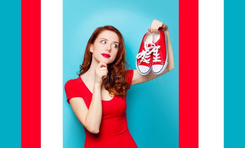 Muchacha en vestido rojo con los gumshoes foto de archivo libre de regalías