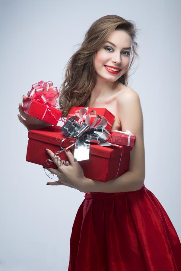 Muchacha en vestido rojo con los regalos el día de tarjetas del día de San Valentín fotos de archivo