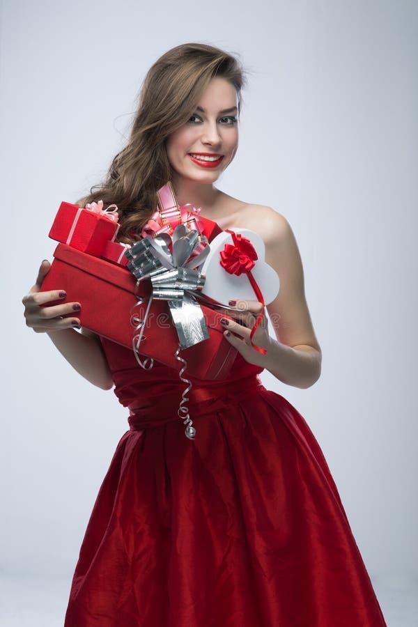 Muchacha en vestido rojo con los regalos el día de tarjetas del día de San Valentín foto de archivo libre de regalías