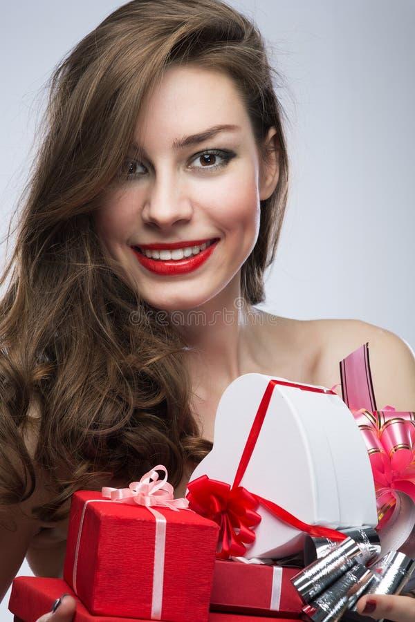 Muchacha en vestido rojo con los regalos el día de tarjetas del día de San Valentín imágenes de archivo libres de regalías