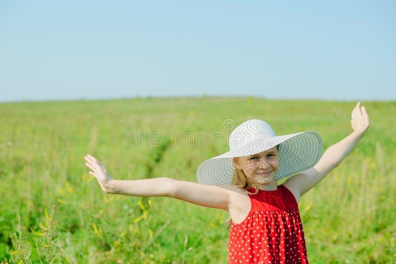 Muchacha en vestido rojo y el sombrero blanco con el borde grande foto de archivo libre de regalías