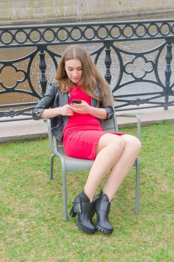 Muchacha en vestido y la chaqueta de cuero con el teléfono a disposición fotos de archivo libres de regalías