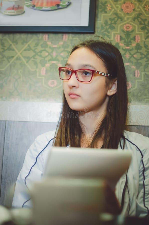 Muchacha en vidrios con el pelo oscuro largo que sostiene una libreta en sus manos foto de archivo libre de regalías