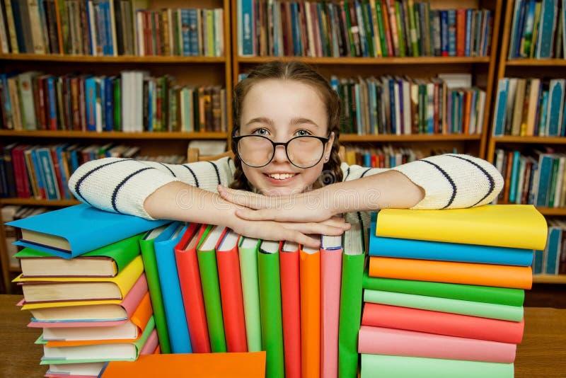 Muchacha en vidrios con los libros en la biblioteca imágenes de archivo libres de regalías