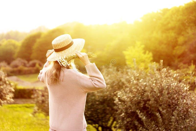 Muchacha en vista posterior del sombrero de paja en la Provence que mira la puesta del sol imagenes de archivo