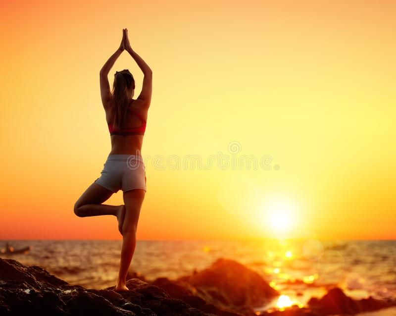 Muchacha en yoga de la actitud de Vrikshasana en la puesta del sol fotografía de archivo