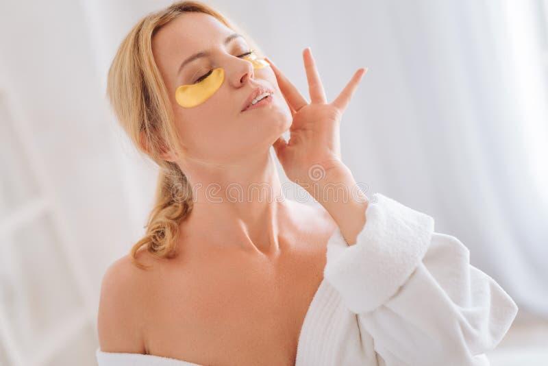 Muchacha encantada que disfruta de su procedimiento de la cara foto de archivo