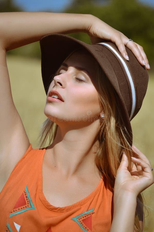 Muchacha encantadora en asolear soñador del sombrero marrón con foto de archivo