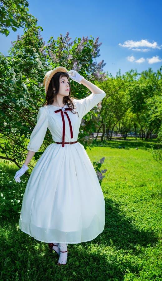 Muchacha encantadora en un vestido blanco y paseos del sombrero de paja imagen de archivo