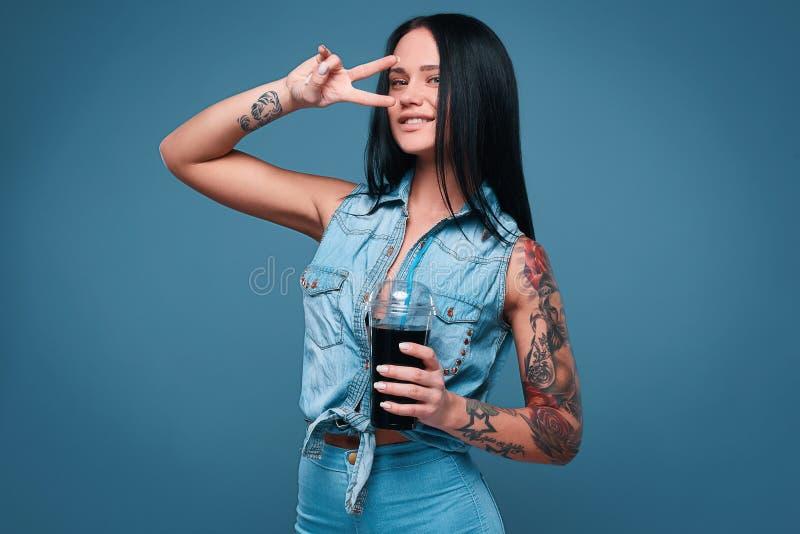 Muchacha encantadora hermosa del tatuaje con soda imagenes de archivo
