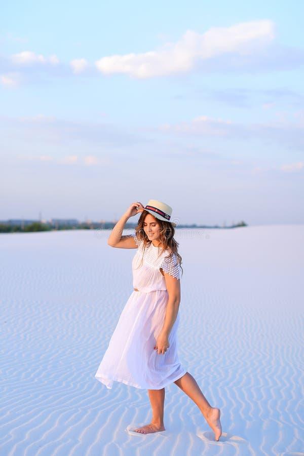 Muchacha encantadora joven en el vestido blanco y el sombrero que van en barefoo de la arena imagen de archivo libre de regalías