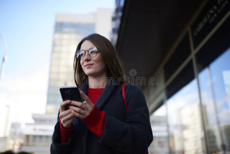 Muchacha encantadora pensativa del inconformista en vidrios de moda que charla con los amigos en redes sociales fotos de archivo