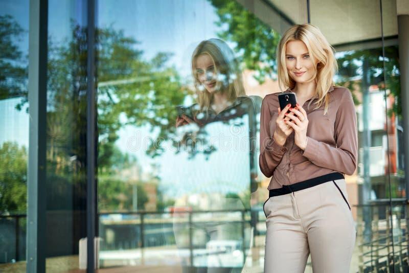Muchacha encantadora que sostiene un teléfono celular de la nueva generación imagen de archivo
