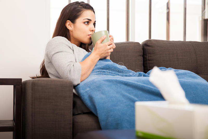 Muchacha enferma que bebe algo de té fotografía de archivo