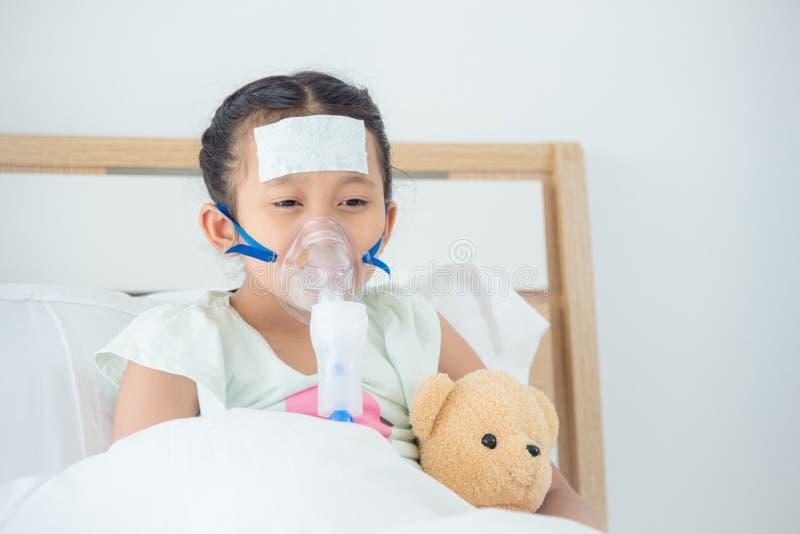 Muchacha enferma que se sienta en cama con la máscara de oxígeno foto de archivo