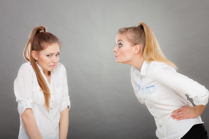 Muchacha enojada de la furia que grita en su amigo o hermana más joven imágenes de archivo libres de regalías