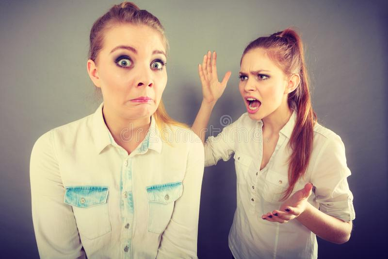 Muchacha enojada de la furia que grita en su amigo o hermana más joven foto de archivo libre de regalías