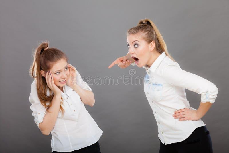 Muchacha enojada de la furia que grita en su amigo o hermana más joven fotos de archivo
