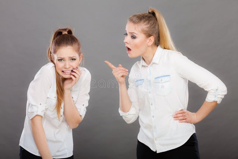 Muchacha enojada de la furia que grita en su amigo o hermana más joven fotografía de archivo libre de regalías