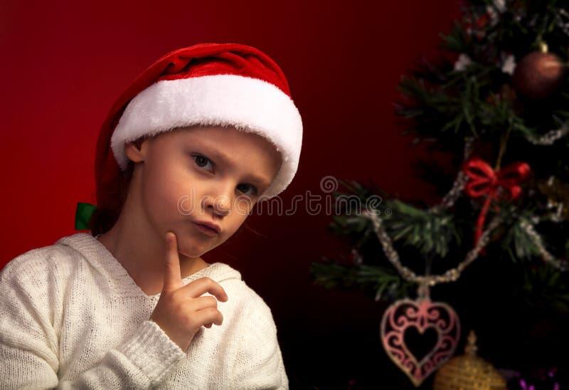 Muchacha enojada linda en el sombrero de Papá Noel de la piel cerca del holida de la Navidad fotografía de archivo