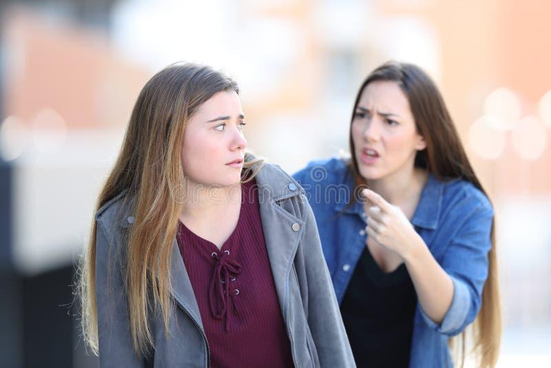 Muchacha enojada que regaña a su amigo confuso en la calle imagenes de archivo