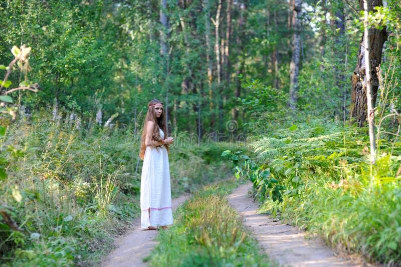 Muchacha eslava hermosa joven con el pelo largo y el traje étnico eslavo que camina a lo largo del rastro en el bosque del verano imágenes de archivo libres de regalías